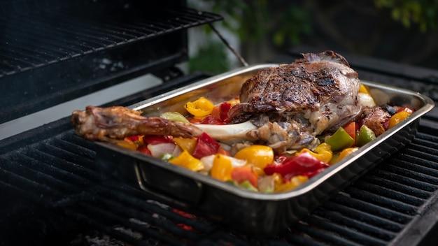 Chef-kok koken een heerlijke lamsbout op een barbecue met kleuren paprika en aardappelen in een metalen dienblad. close-up van smakelijk geitenvlees in bbq van tuinhuis bij vakantievakanties. gebraden grillvoedsel in spanje.