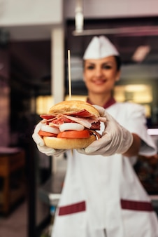 Chef-kok koken en versierde hamburger. hamburger concept koken