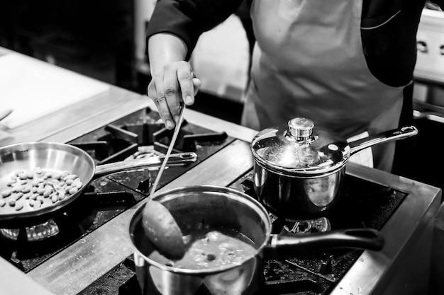 Chef-kok koken in een keuken, chef-kok op het werk, zwart-wit
