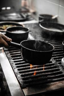 Chef-kok koken van voedsel in een zwarte pan op een vuur