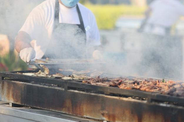 Chef-kok kokend vlees op houtskool buiten hotelclose-up