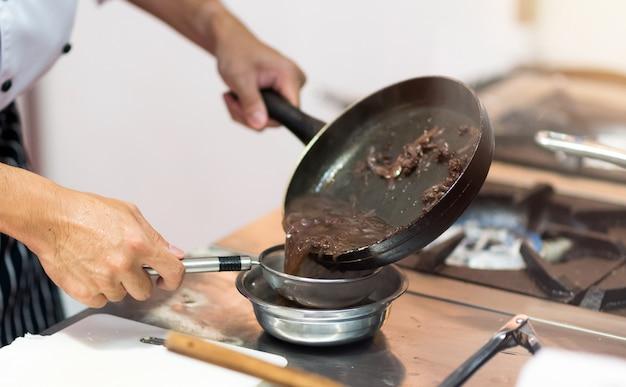 Chef-kok kokend voedsel in de keuken, chef-kok die voedsel voorbereidt