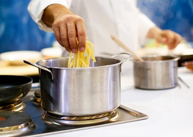Chef-kok kokende spaghetti in de keuken