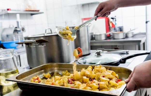 Chef-kok kookt gebakken aardappelen met stukjes vlees in de keuken van een restaurant