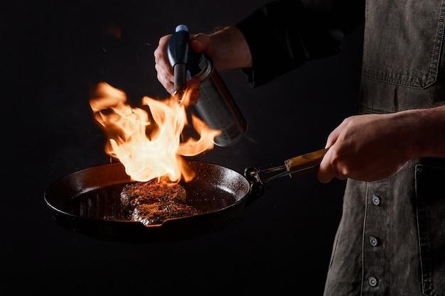 Chef-kok kookt hamburgers, braadt gehaktballen op open vuur