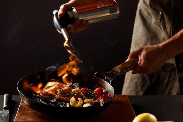 Chef-kok kookt met vuur in een pan garnalen met groenten