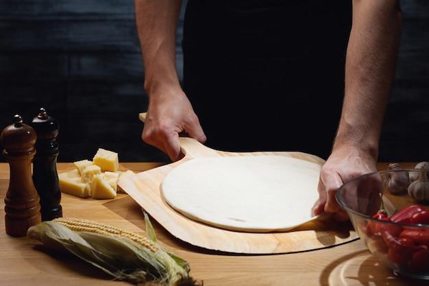 Chef-kok kookt pizza, lege pizzabodem aan boord