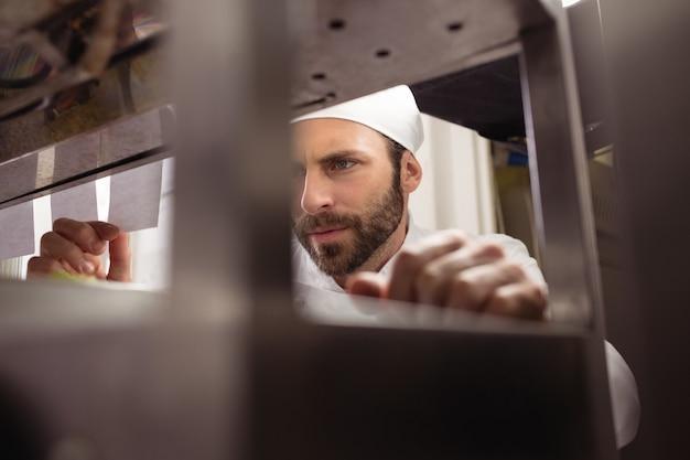 Chef-kok lezen van zijn bestelling op notitie in aanrecht