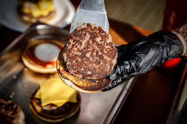 Chef-kok maakt een hamburger in zwarte handschoenen. haalt ingrediënten op
