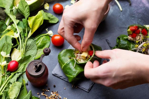 Chef-kok maakt een veganistische wrap met rode paprika's en tomaten