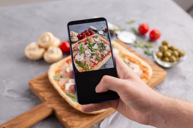 Chef-kok maakt foto's van de gekookte italiaanse pizza met parmaham op smartphone en fotografeert eten