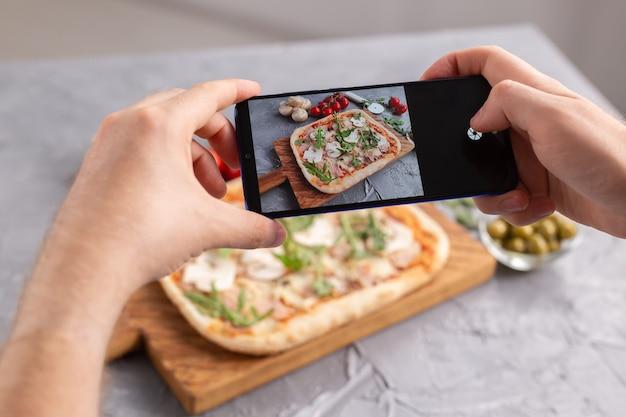 Chef-kok maakt foto's van de gekookte italiaanse pizza met parmaham op smartphone. fotograferen van voedsel en sociale netwerken concept.