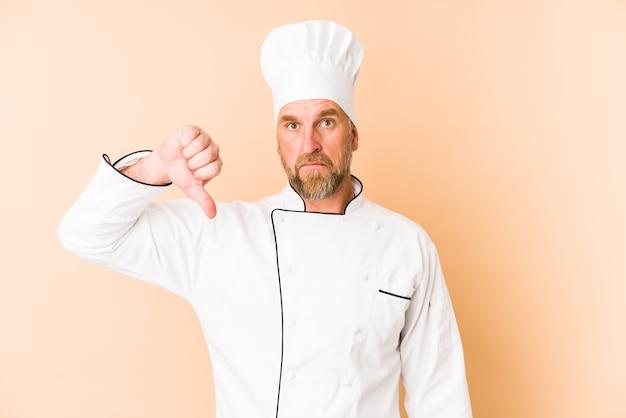 Chef-kok man geïsoleerd op beige muur met een afkeer gebaar, duimen naar beneden. meningsverschil concept.