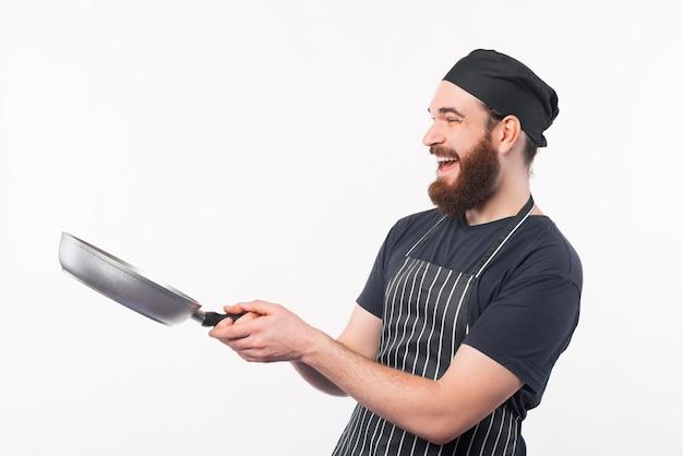 Chef-kok man glimlachend en pan over wit gebruiken