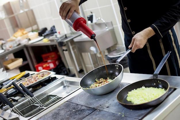 Chef-kok man koken op industriële keuken