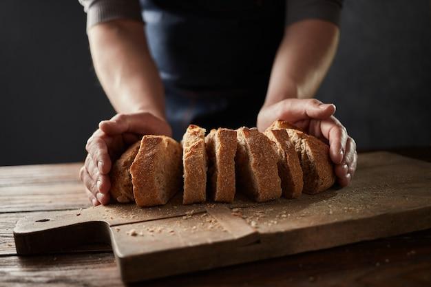 Chef-kok met de hand zelfgemaakt gesneden brood snijden