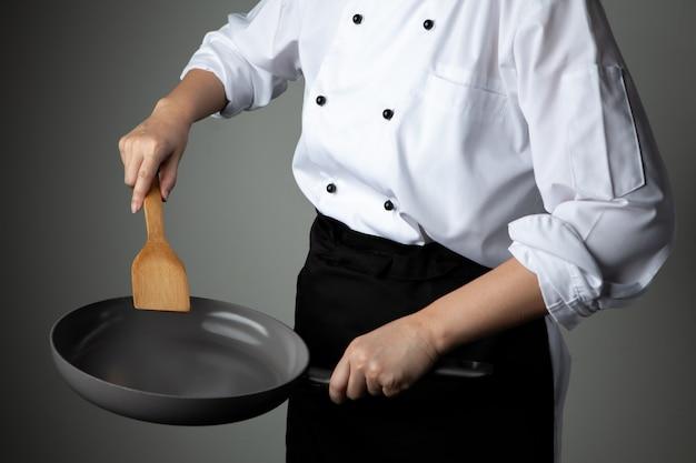 Chef-kok met de pan van de handgreep op grijze achtergrond