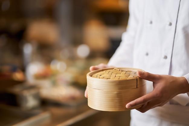 Chef-kok met een ronde bamboedoos in de keuken