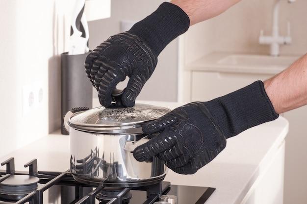 Chef-kok met hete pan in beschermende handschoenen