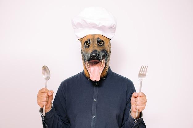 Chef-kok met hondenmasker toont lepel en vork om te eten
