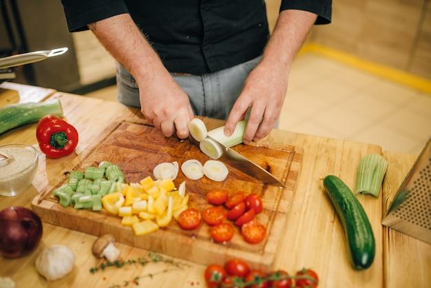 Chef-kok met mes snijdt champignons op een houten bord