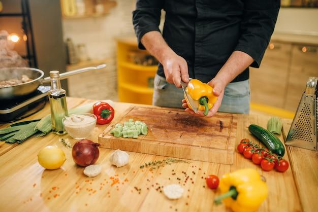Chef-kok met mes snijdt gele peper op een houten bord