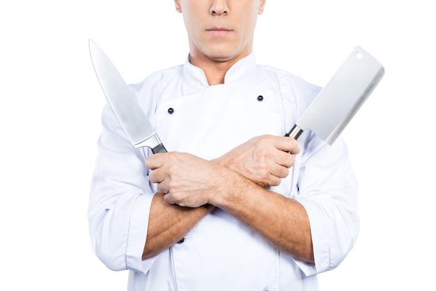 Chef-kok met messen. close-up van zelfverzekerde volwassen chef-kok in wit uniform met messen in zijn handen terwijl hij tegen een witte achtergrond staat