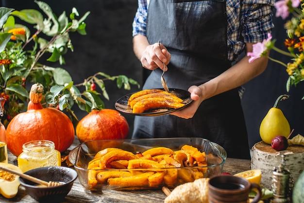Chef-kok met plakjes gebakken oranje pompoen met honing en kaneel