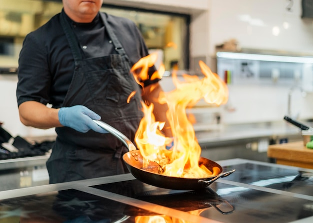 Chef-kok met schort en handschoenen flambeing schotel