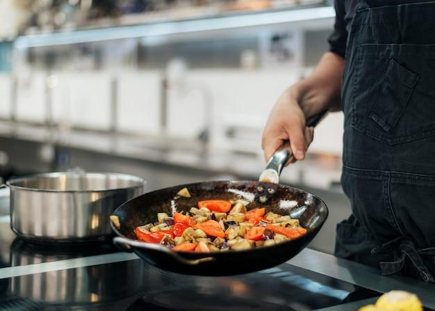 Chef-kok met schort kookschotel in de keuken
