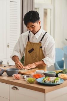 Chef-kok neemt rijst voor sushi-broodjes en bereidt ingrediënten voor het maken van online bezorgservice voor sushi