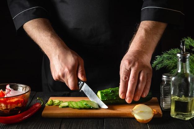 Chef-kok of kok die een groene komkommer snijdt in de keuken in het restaurant. een heerlijke salade maken met verse groenten