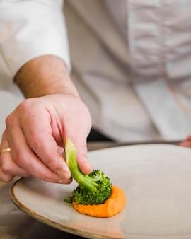 Chef-kok onderdompelende broccoli in saus