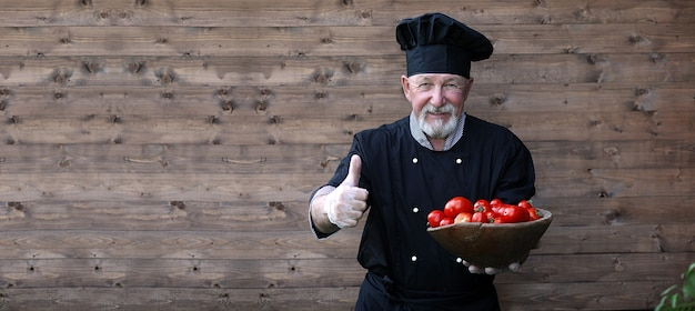Chef-kok oud in uniform met verse groenten op een houten bacground