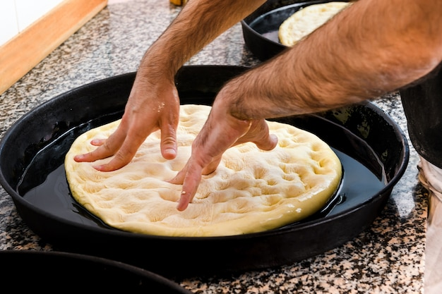 Chef-kok pizza deeg uitrekken in een dienblad