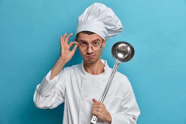 Chef-kok poseert bij commerciële keuken, kijkt serieus door glazen, houdt pollepel vast, bereidt maaltijd, gerecht klaar om te koken, luistert naar advies