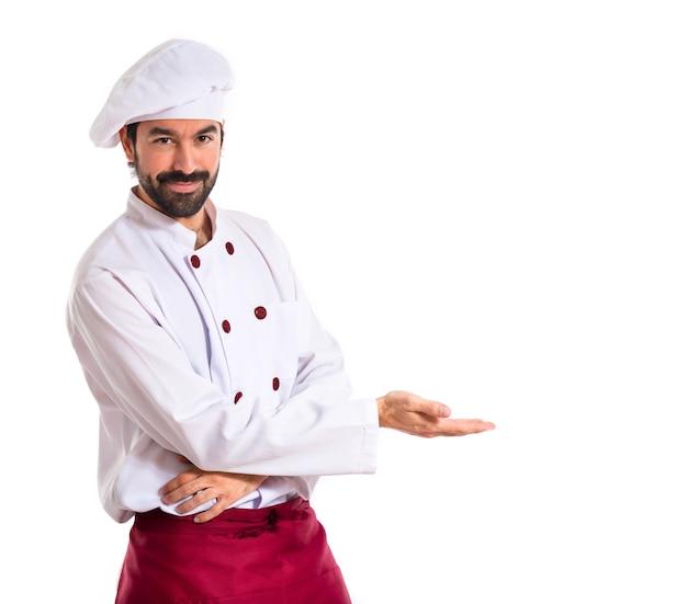 Chef-kok presenteert iets over witte achtergrond