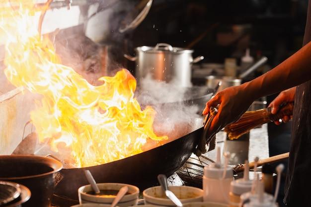 Chef-kok roerbak bezig met koken in de keuken. chef roerbak het eten in een koekenpan, rook en spetter de saus in de keuken.