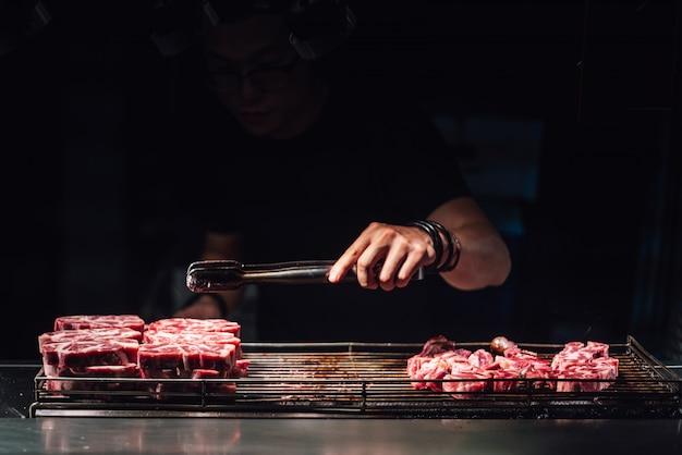 Chef-kok selecteert een rauwe runderblokje per tong voor het koken met fakkel in medium rood.