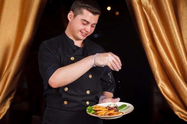 Chef-kok serveert caesar salade met parmezaanse kaas. chef-kok die een salade voorbereidt.
