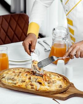 Chef-kok serveert lamsgerecht bedekt met gesmolten kaas