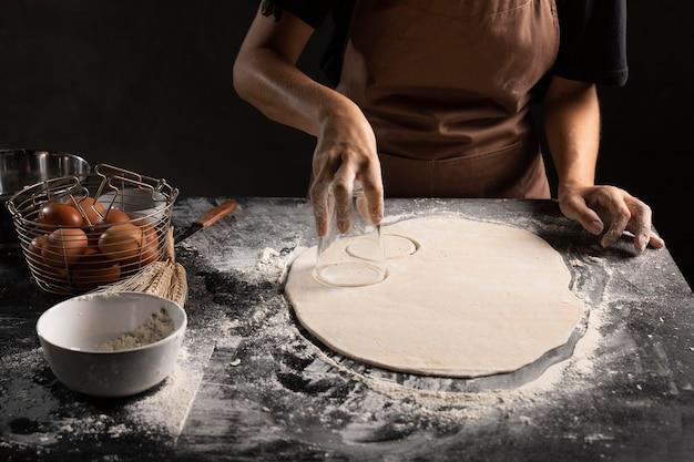 Chef-kok snijden omcirkeld van deeg op tafel