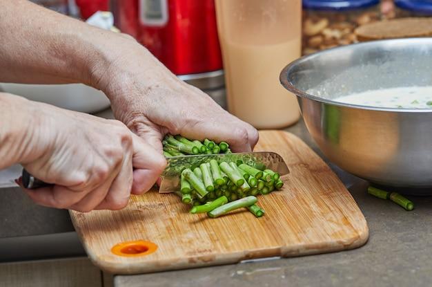 Chef-kok snijdt asperges met mes om gebakken goederen te maken met asperges en erwten. stap voor stap recept.
