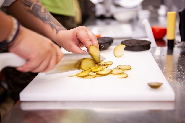 Chef-kok snijdt augurken voor heerlijke hamburger in restaurant. voedsel voorbereiding