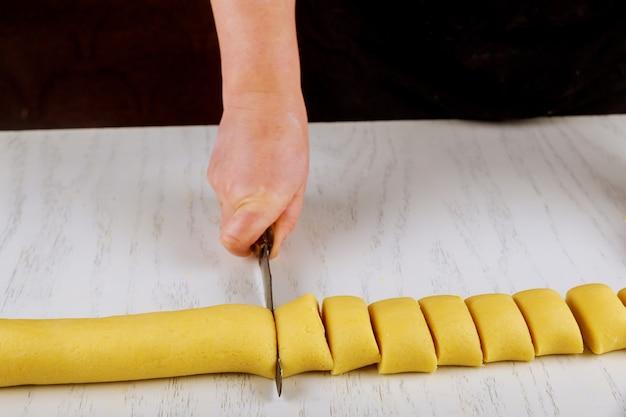 Chef-kok snijdt deeg met een mes in gelijke portie voor het koken van koekjes.