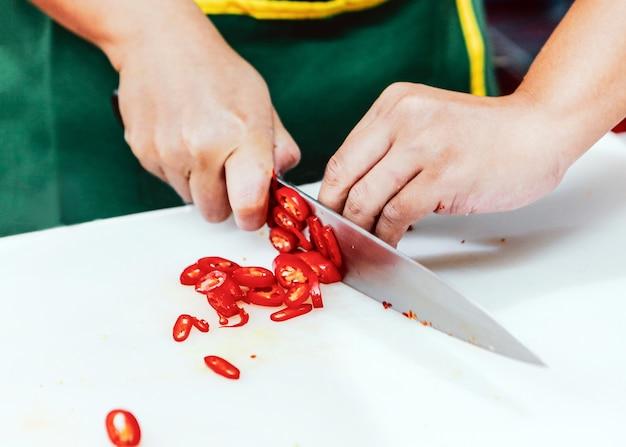 Chef-kok snijdt groenten in de keuken, chef-kok koken, chef-kok bereiden van voedsel