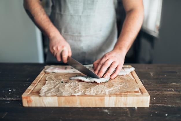 Chef-kok snijdt rauwe visplakken op houten snijplank