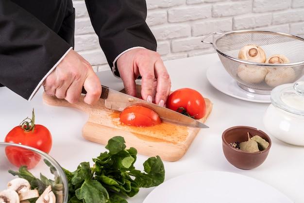 Chef-kok tomaten snijden
