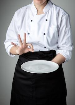 Chef-kok uniform met witte lege plaat welkom huidige gerecht restaurant promotie
