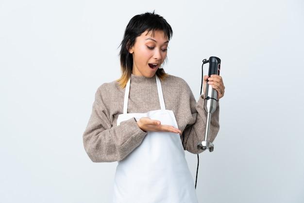 Chef-kok uruguayan meisje die handmixer over geïsoleerde witte muur gebruiken die copyspace denkbeeldig op de palm houden